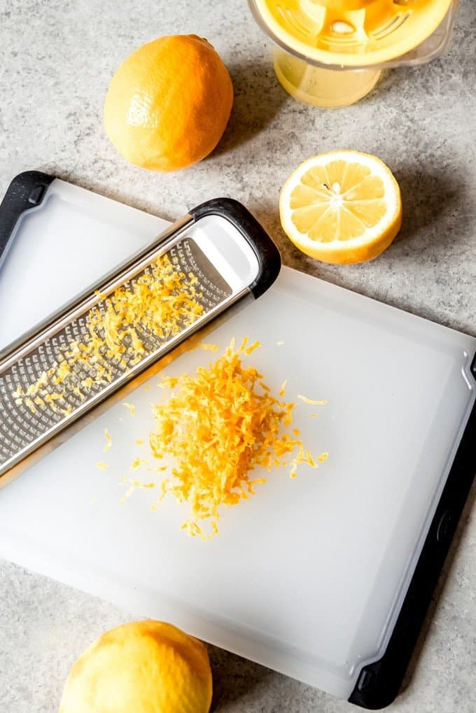 An image of Meyer lemon zest and lemons being juiced.