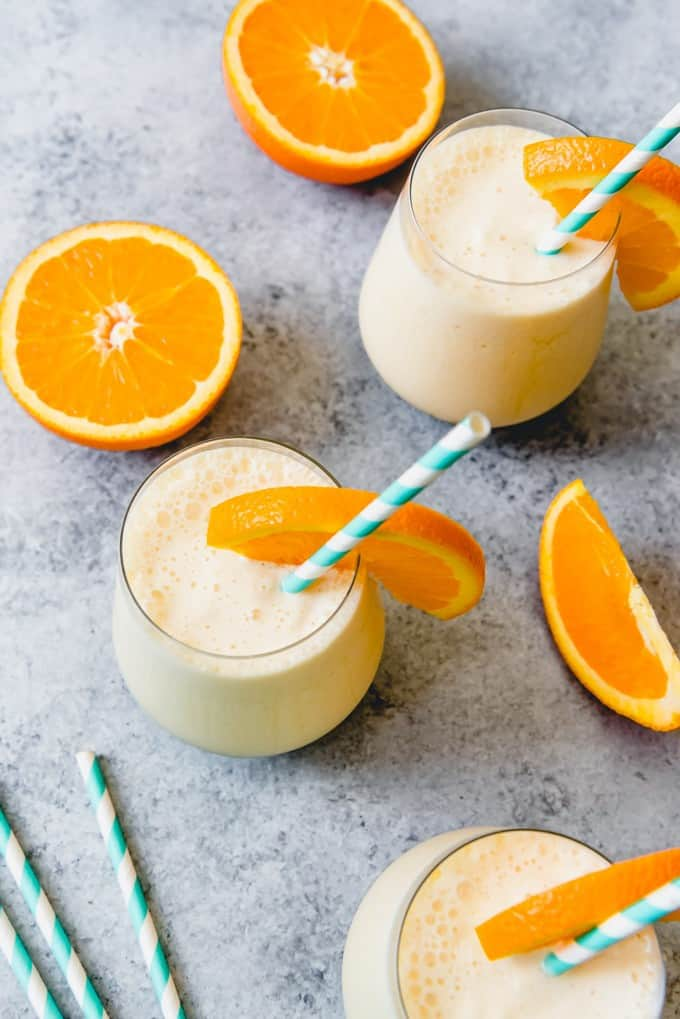 An image of glasses of an orange julius smoothie with slices of oranges and straws.