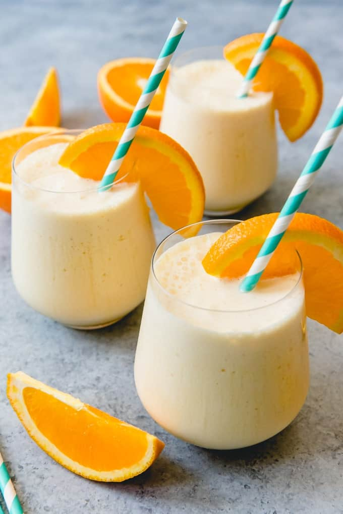 An image of three glasses with a creamy, fruit smoothie with milk known as an orange julius.