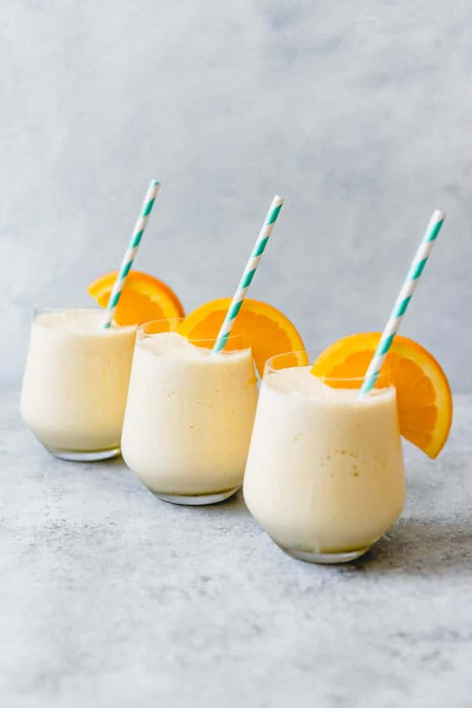 orange slice garnished cups of orange julius with striped straws inside