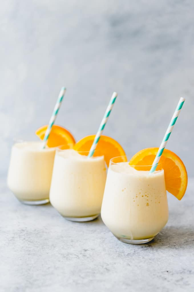 three glasses of orange julius with orange garnishes and striped straws inside