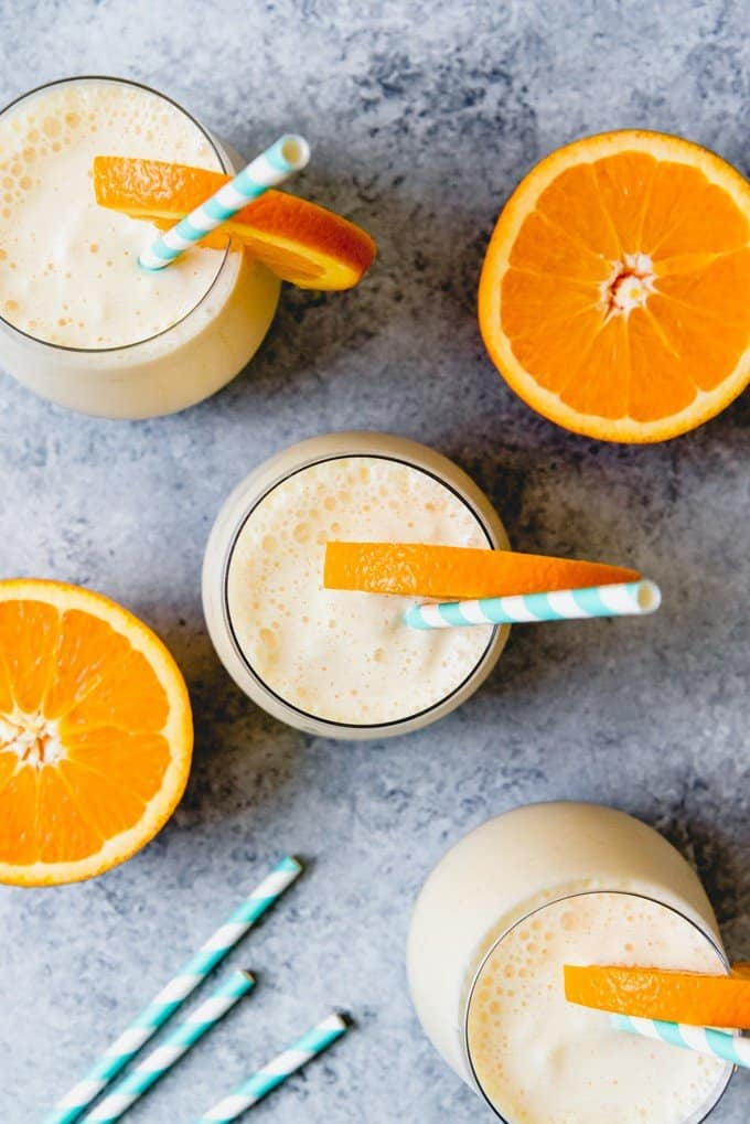 An image of a copycat orange julius recipe in glasses with orange slices and straws.