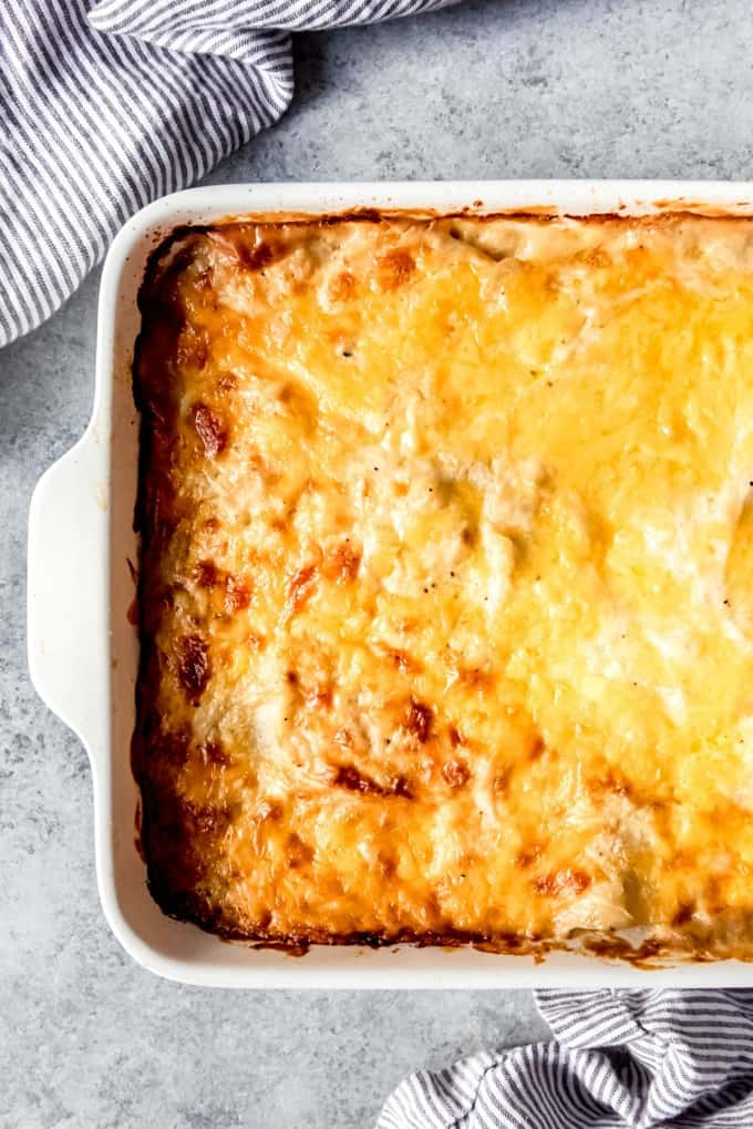 An image of a pan of cheesy scalloped potatoes with a golden brown crust of melted cheese on top.