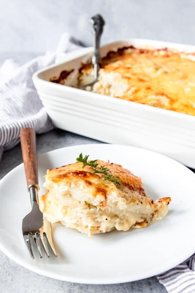 An image of a serving of cheesy au gratin potatoes on a plate next to a casserole dish full of this easy Easter side dish.