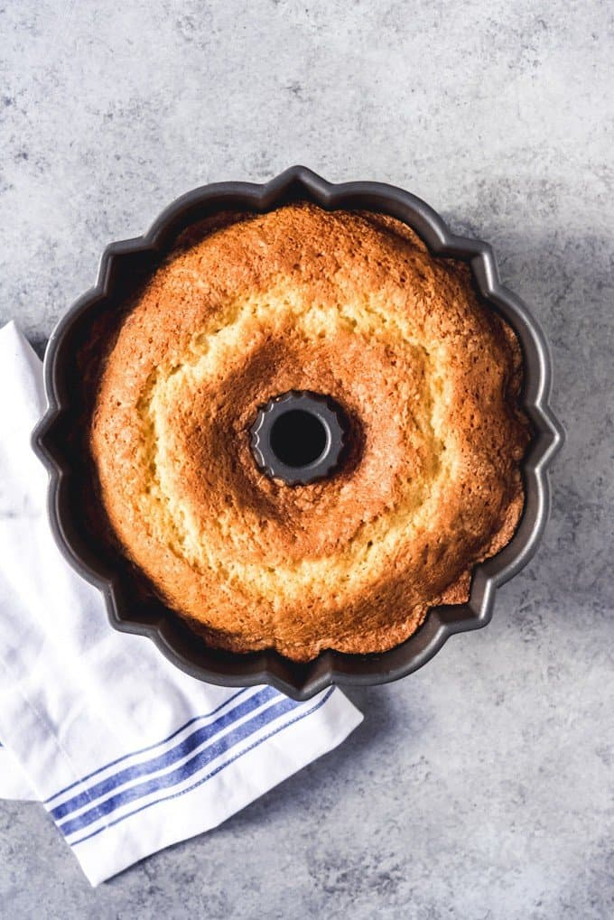 An image of a pound cake baked in a bundt pan before being turned out onto a serving plate.