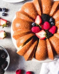 sour cream pound cake filled with mixed berries and a slice cut