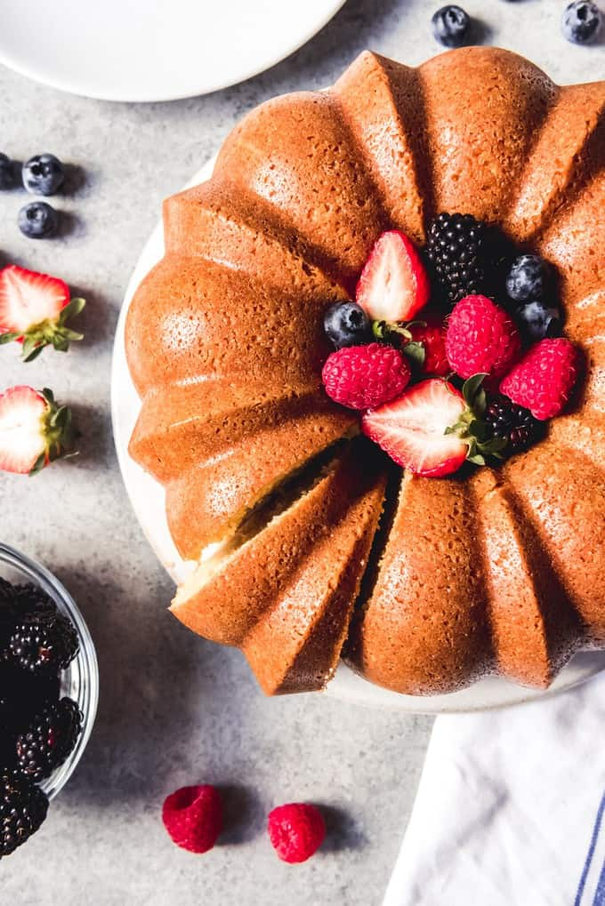 An image of a sour cream pound cake with a slice cut out of it.