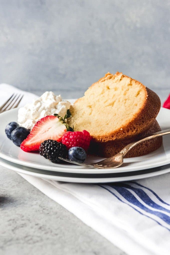 An image of a slice of sour cream pound cake served with berries and whipped cream on the side.