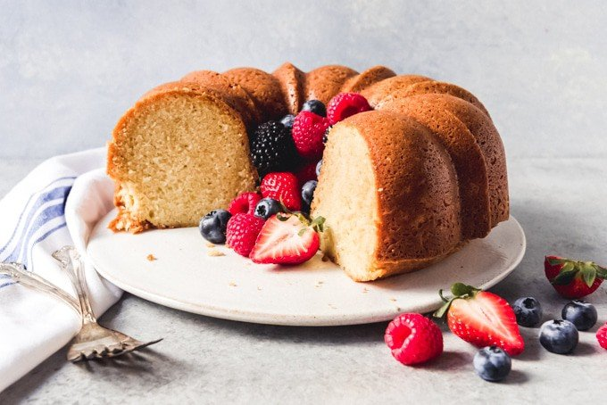 An image of a classic bundt cake recipe for sour cream pound cake served simply with fresh seasonal spring berries.