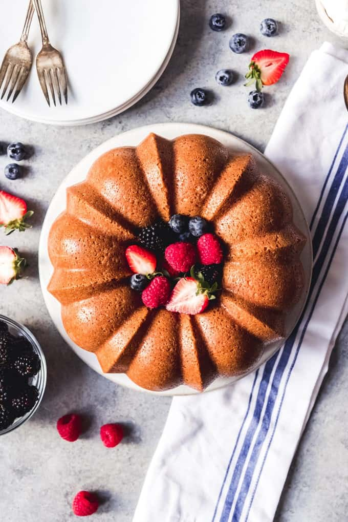 An image of a pound cake made in a bundt cake pan with fresh berries.