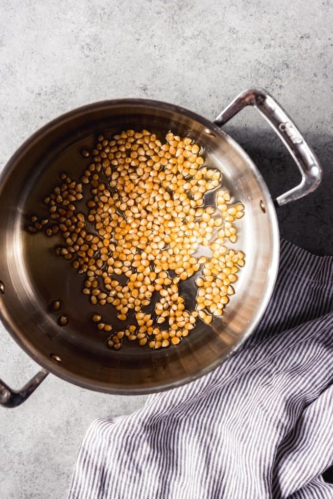An image of popcorn kernels and hot olive oil in a pan for making stovetop popcorn.