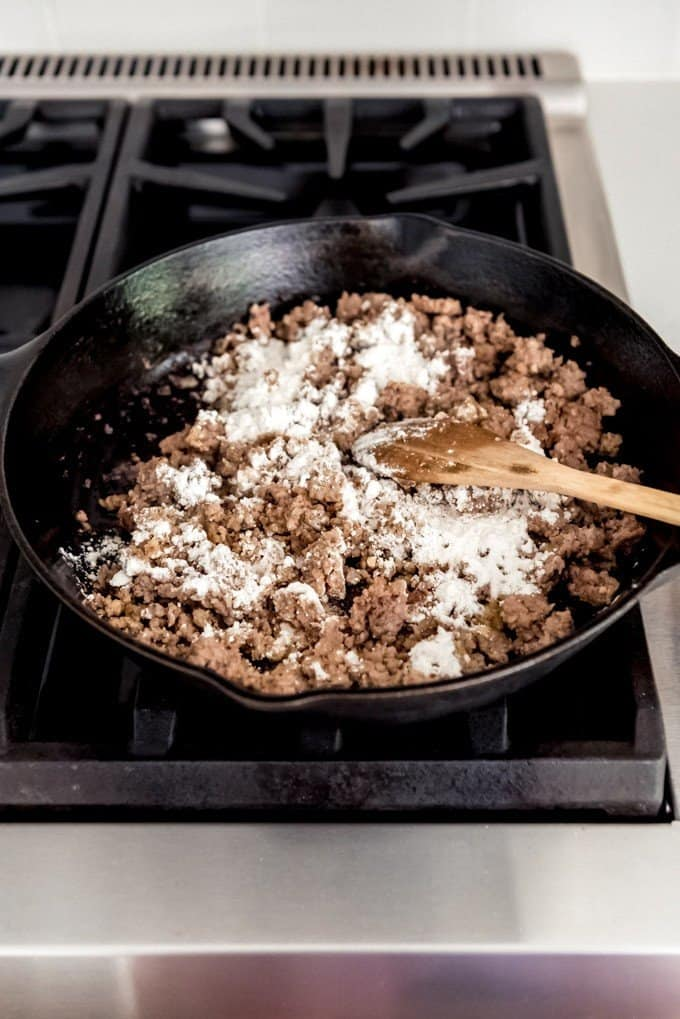 An image of breakfast sausage being browned in a cast iron skillet with a little flour to make a gravy.