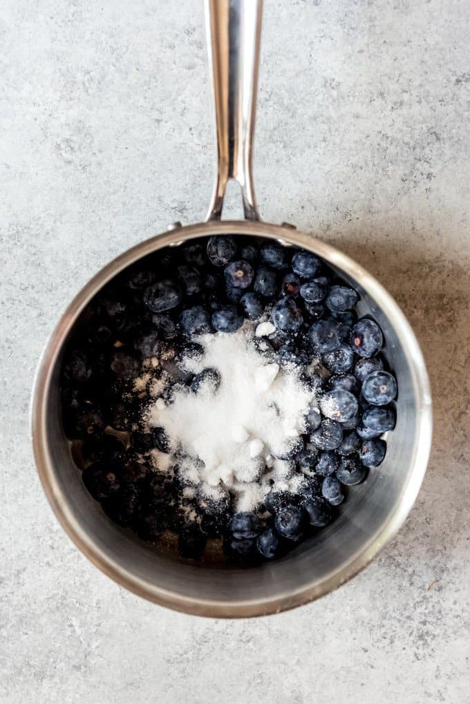 An image of blueberries and sugar in a saucepan.