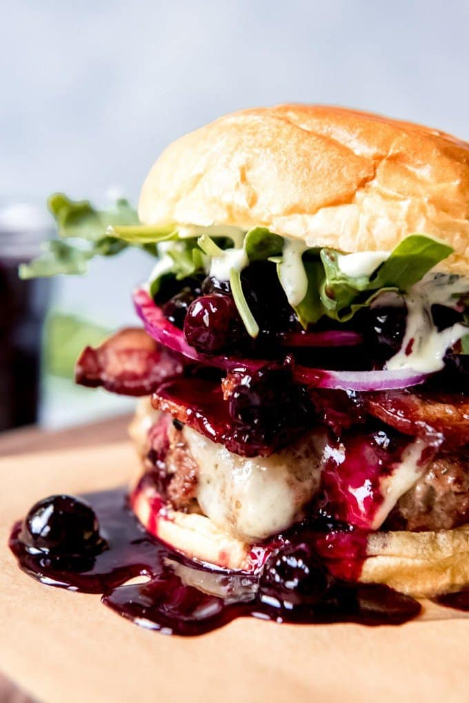 An sideview image of a tall hamburger with cheese, bacon, onions, arugula, basil aioli, and a blueberry balsamic compote.