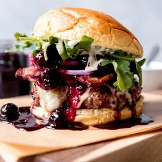 This Red, White, and Blueberry Bacon Burger with Basil Aioli is a mouthful in every sense!  A perfectly seasoned and grilled hamburger get topped with rich havarti cheese, blueberry balsamic compote, red onions, arugula, and an easy basil aioli, all on a brioche bun.  Perfect for Memorial Day, the 4th of July, or any other day of the year! #ad #SummerGrilling #TheSpiceHouse #burger #cheeseburger #cheese #blueberries #grilling #4thofJuly #havarti #aioli #basil #recipe #bacon