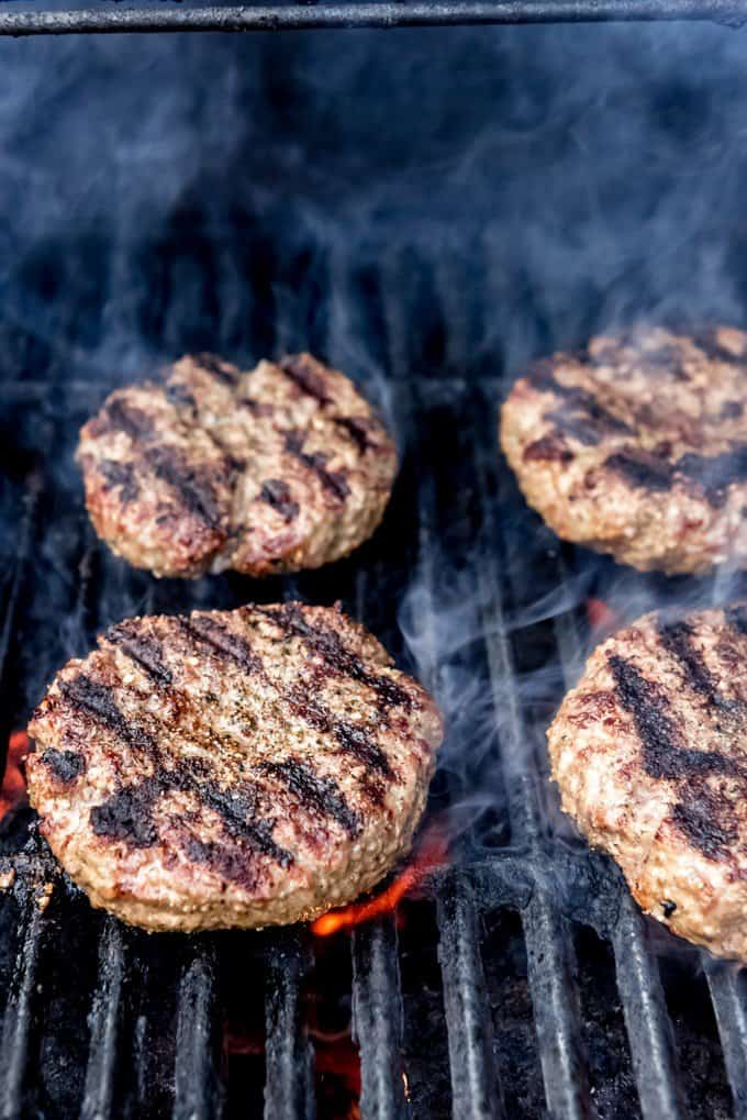 Burgers with grill marks on a grill over flames with smoke.