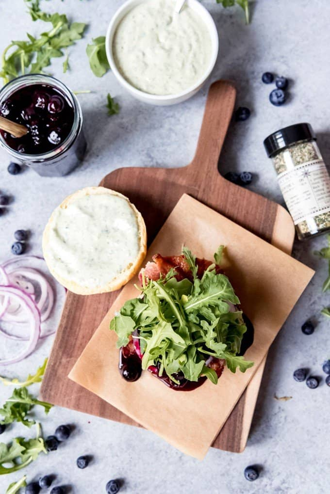 An image of a blueberry bacon burger being assembled on a cutting board.