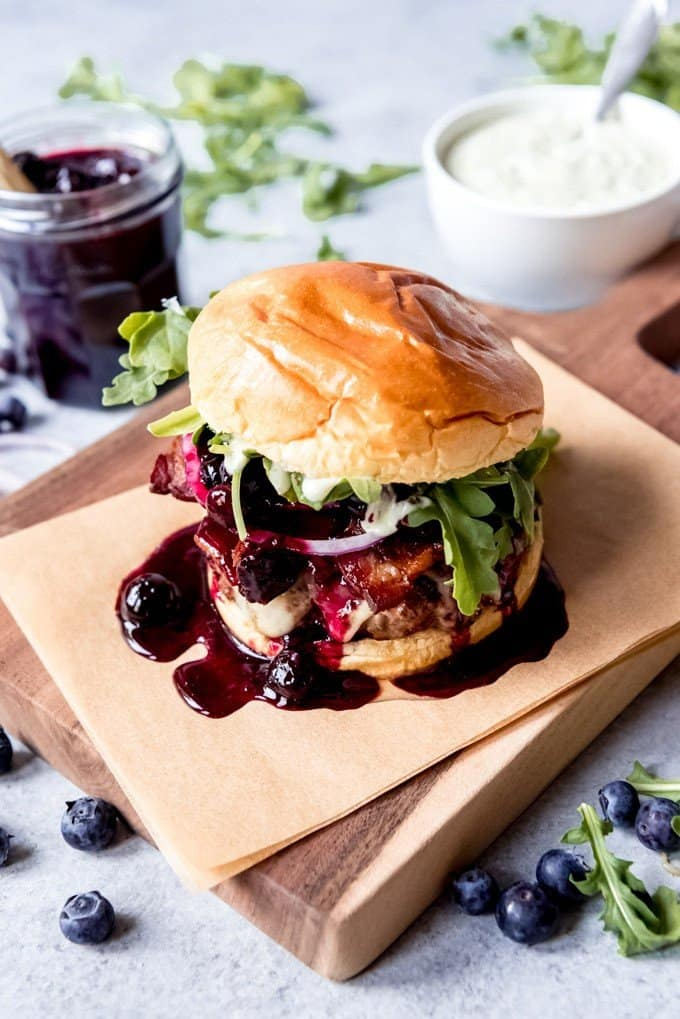 An image of a gourmet burger with blueberry sauce on a cutting board.