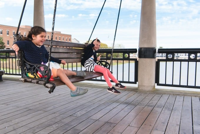 An image of girls swinging on a bench at Waterfront Park in Charleston, South Carolina.