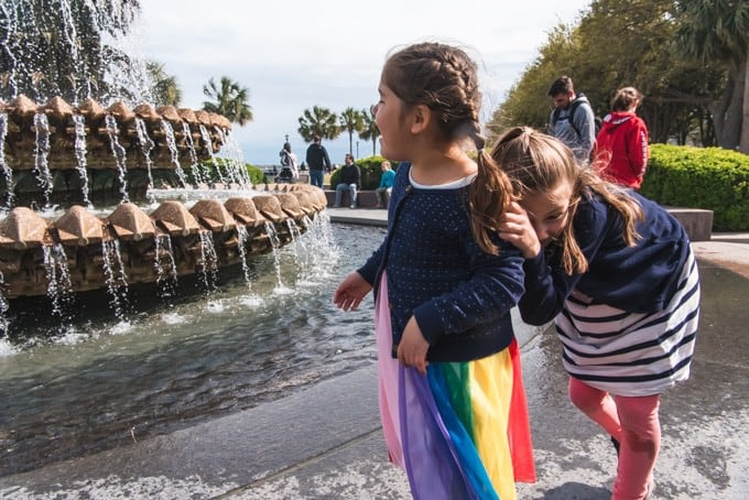 An image of two girls playing at the pineapple fountain in Waterfront Park in Charleston, South Carolina.