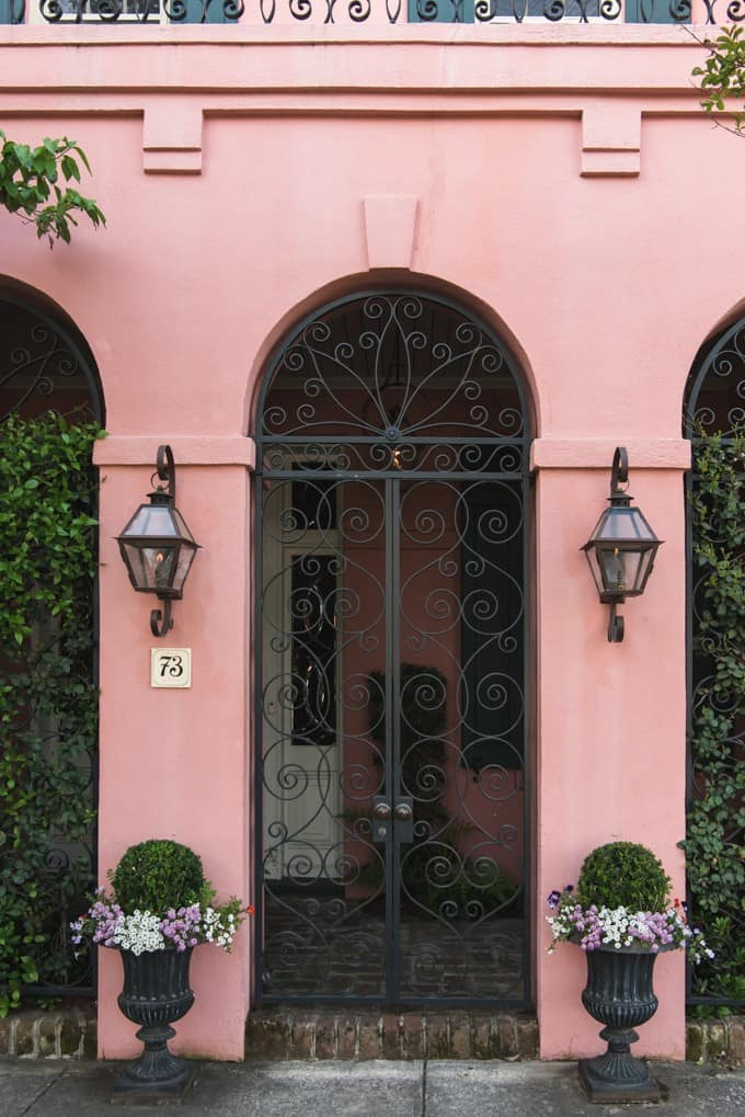 An image of wrought iron gates on a pink house on Rainbow Row in Charleston, South Carolina.