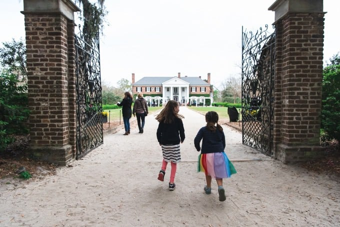 An image of two girls running through the gates of Boone Hall Plantation.