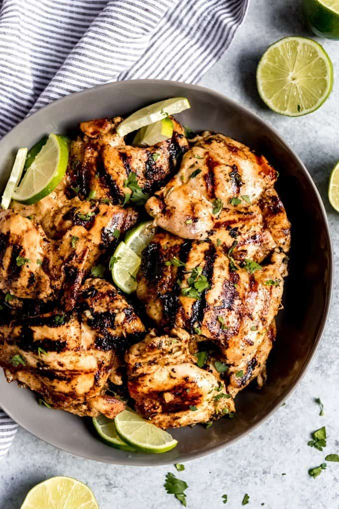 An image of a grey serving plate with grilled chicken thighs, sliced limes, and chopped cilantro sprinkled over the top.