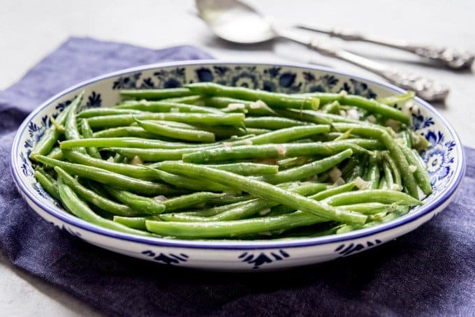 An image of a blue and white Delft serving dish with haricot verts.
