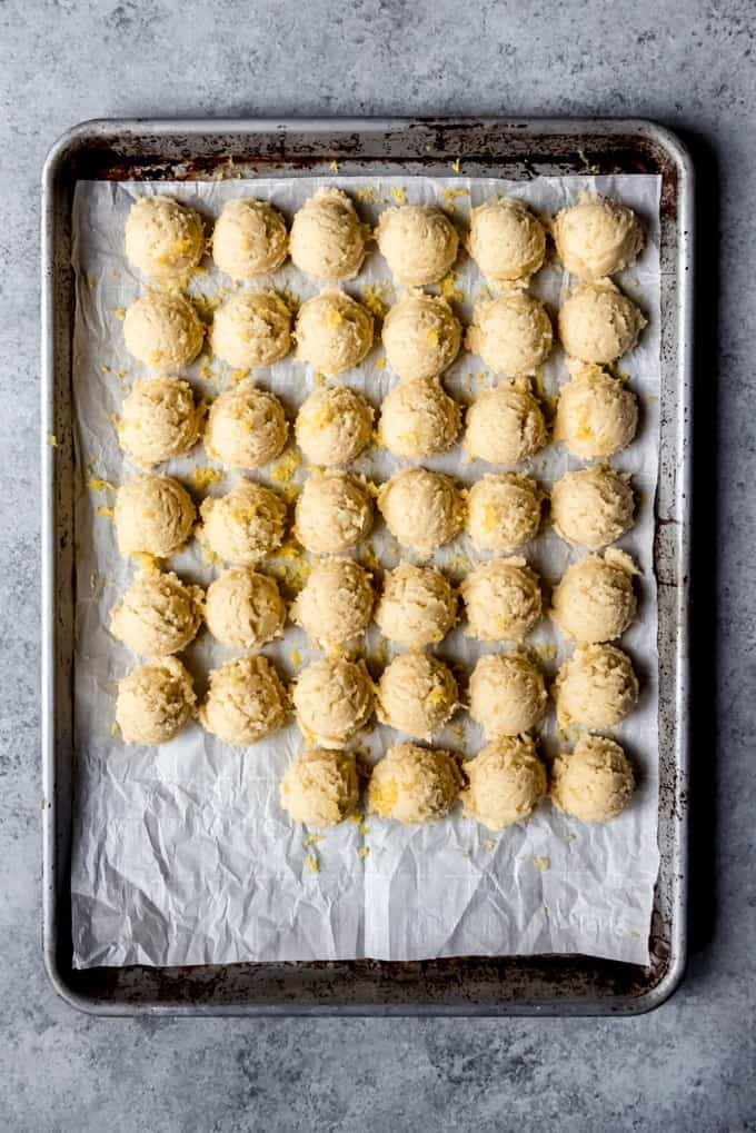 An image of balls of lemon sugar cookie dough lined up in rows on parchment paper.