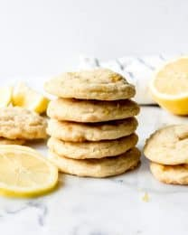 stacked lemon cookies with cookie and lemon slices to the sides