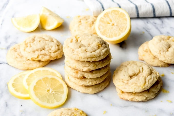 An image of lemon cookies stacked on top of each other next to slices of fresh lemon.