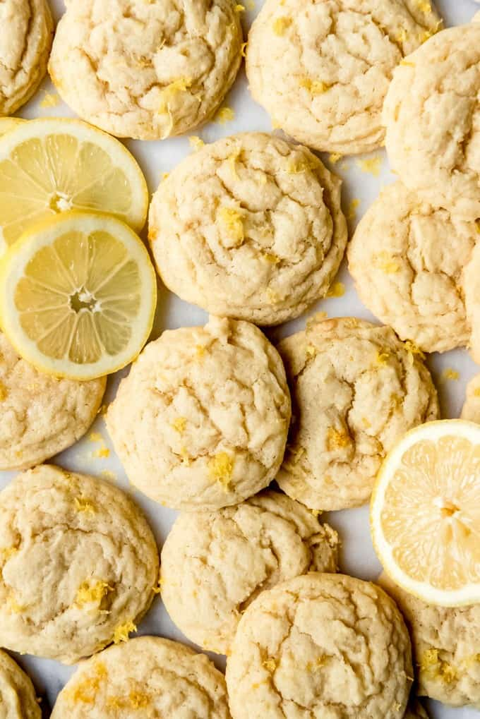An image of soft and chewy lemon cookies with lemon zest and slices of lemon around them.