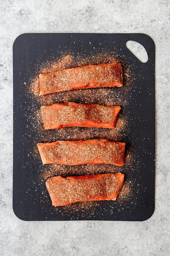 An image of four coho salmon fillets sprinkled with a homemade spice rub for making blackened salmon tacos.