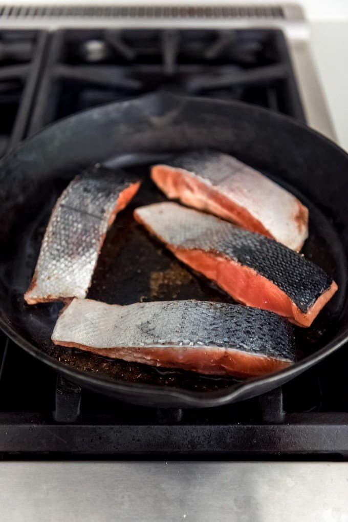 An image of salmon fillets in a cast iron skillet.