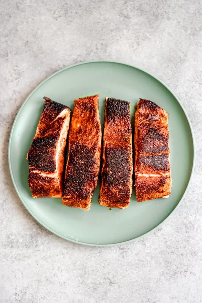 An image of four cooked blackened salmon fillets on a green plate.