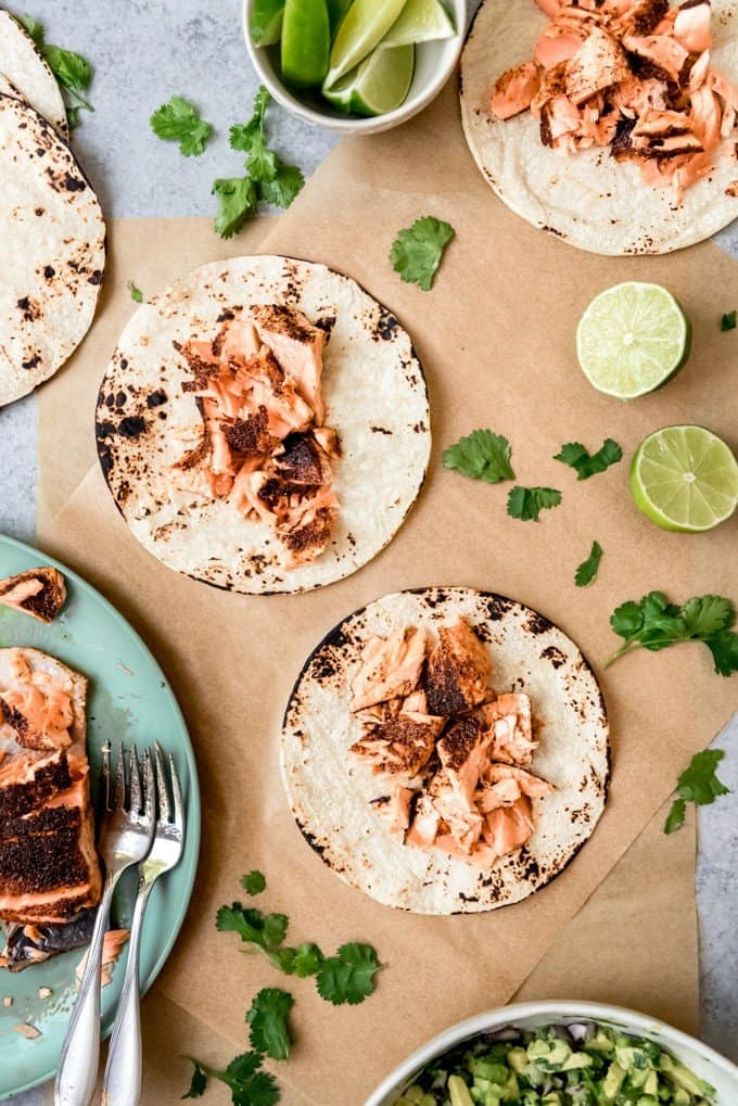 An image of spicy salmon that has been flaked and piled on charred corn tortillas for fish tacos.