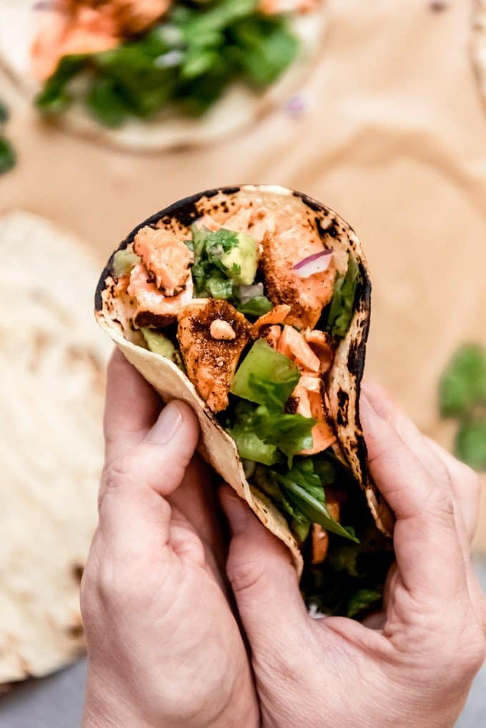 An image of hands holding a salmon taco.