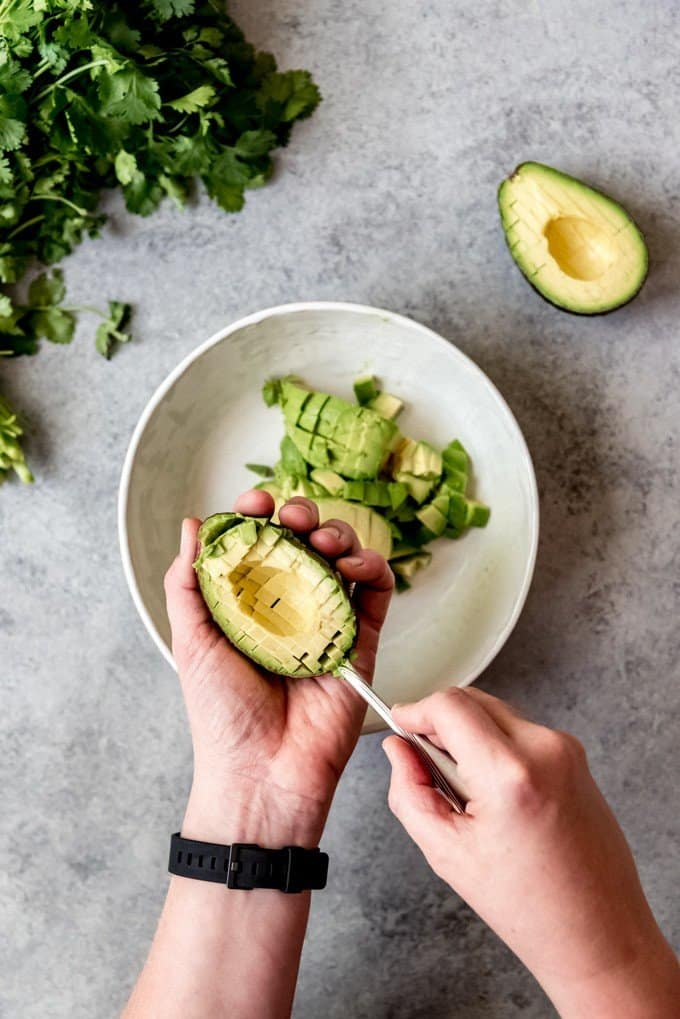 An image of a hand using a spoon to scoop diced avocado out of the avocado skin and into a bowl.