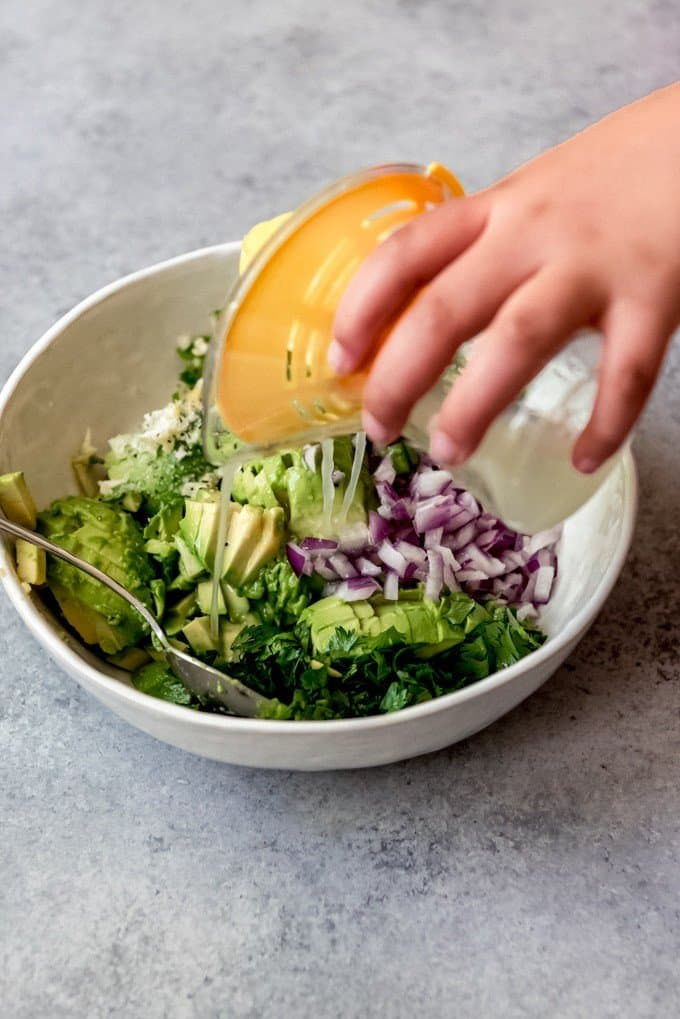 An image of a hand pouring lime juice over avocado salsa.