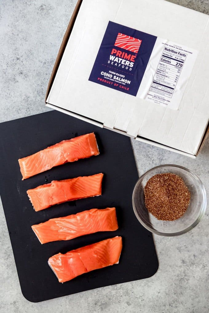 An image of four coho salmon fillets on a cutting board next to a Prime Waters Seafood box and a homemade spice rub.