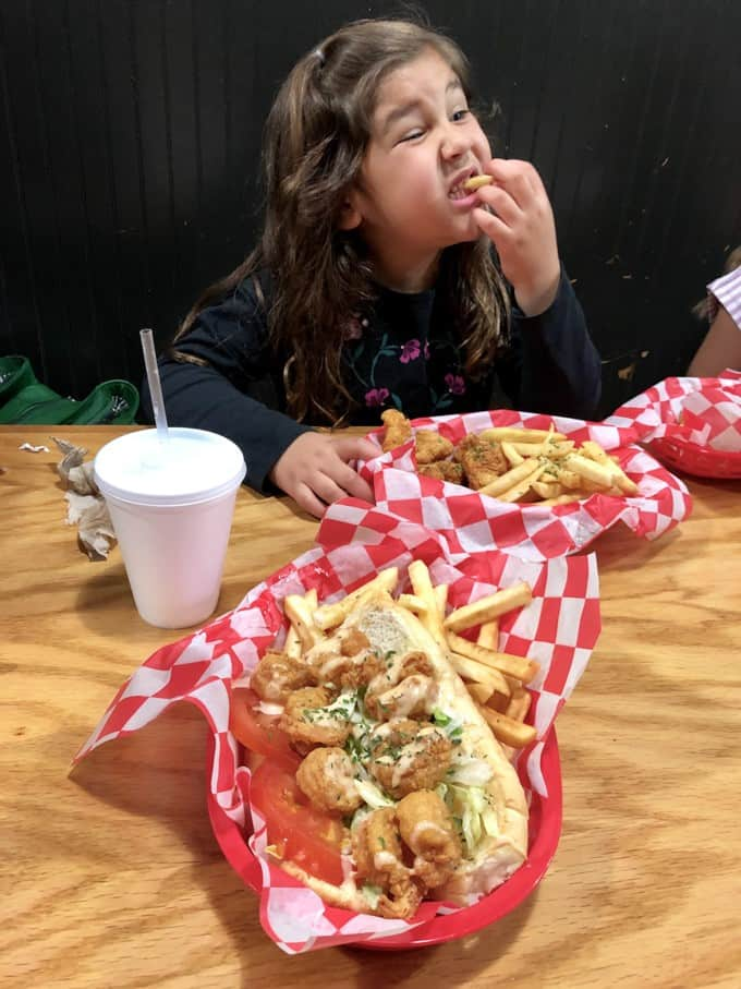 An image of a shrimp po' boy with a child eating french fries at a restaurant booth.