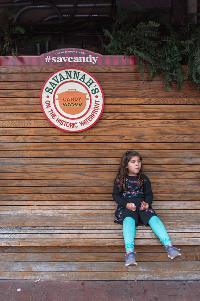 An image of a child sitting on a bench in front of Savannah's Candy Kitchen in Savannah, Georgia.