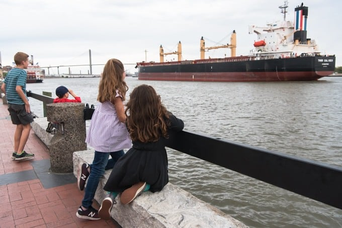 An image of children watching a large container ship on the Savannah River.