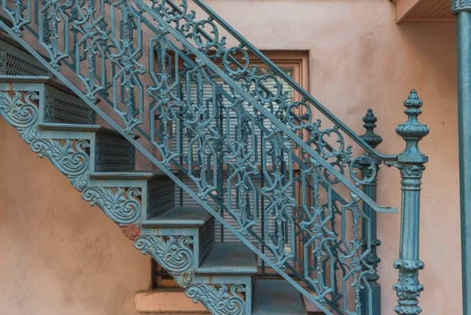 Detail of an intricate green wrought iron staircase.