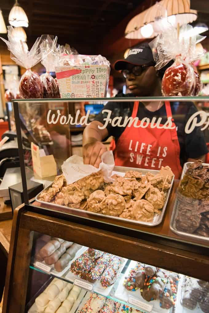 An image of an employee grabbing pecan pralines at River Street Sweets in Savannah, Georgia.
