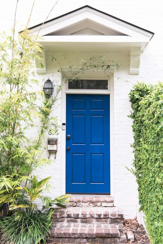 An image of a blue door on a white painted brick house.