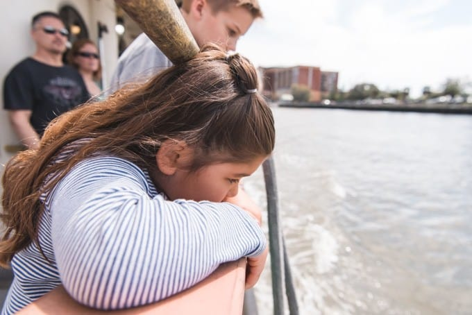 An image of a girl looking over the side of a ferry on the Savannah River.