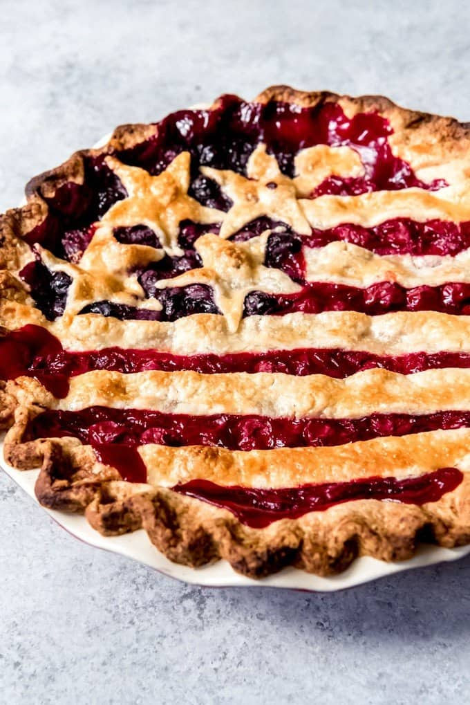 An image of a cherry and blueberry pie decorated like the American flag.