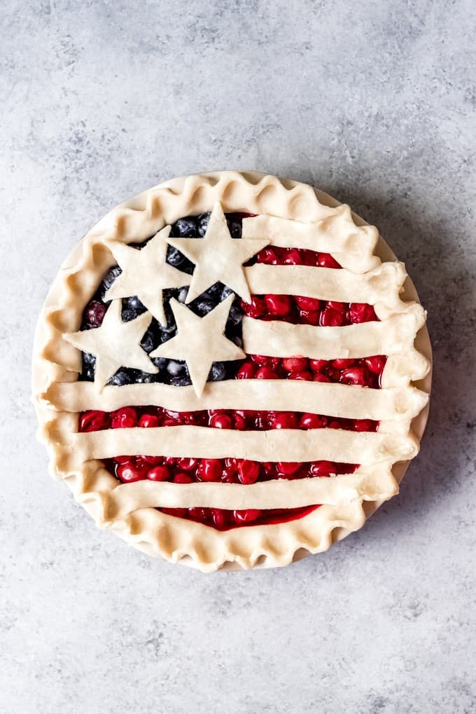 An image of an unbaked cherry and blueberry pie that is decorated with strips of pie dough and stars of cut-out pie dough for a crust.