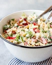 A large bowl of an easy pasta salad with tomatoes, lettuce, bacon, and bowtie pasta.